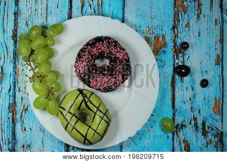 Donuts with green and chocolate icing/ Donuts with green and chocolate icing and pink topping on blue wooden background.