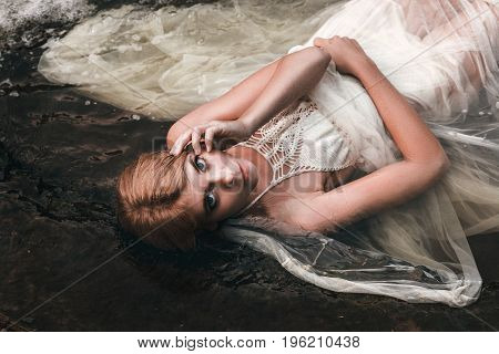 beautiful young cute girl in the water in openwork clothes