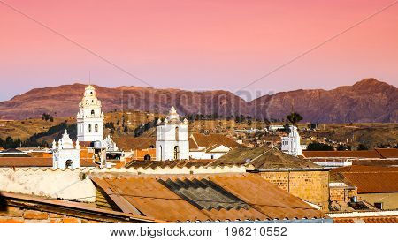 White colonial bell towers and orange rooftops in Sucre, Bolivia, South America.