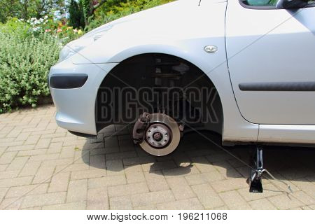 Car on jack to be repaired in the backyard of a house