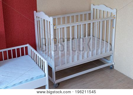 The nursery has two Cribs. One cot for toddlers and one for older children. Crib white. On the mattresses in the covers.