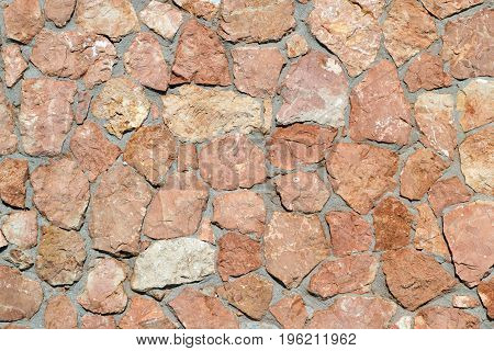 Texture in brown tones. Wall made of natural natural stone granite and sandstone