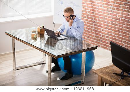 Businessman Sitting On Blue Fitness Ball Using Laptop In Modern Office