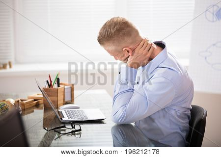 Businessman Sitting At Desk With Laptop Having Neck Pain In Office