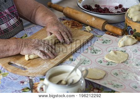 Grandmother home cooks the dumplings with cherries