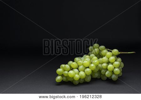 White grapes lying on a dark background