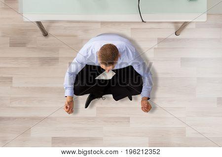 Businessman Sitting On Hardwood Floor Doing Meditation In Office