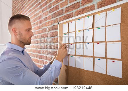 Close-up Of A Businessman Looking At Notes Attached On Bulletin Board