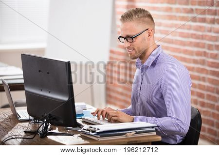 Happy Confident Businessman Wearing Eyeglasses Working On Computer In Office