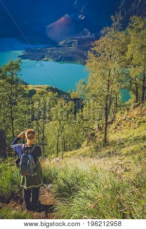 Caucasian girl with small backpack photographing the crater and cone of the Gunung Rinjani volcano, Lombok island, Indonesia