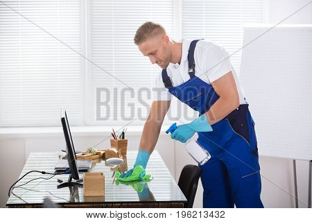 Portrait Of A Smiling Male Janitor Cleaning Desk With Cloth At Workplace