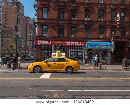 New York NY USA -- July 12 2017 -- A cab is stopped on 14th street waiting for the light to change while two pedestrians begin crossing the street in New York's Greenwich Village. Editorial Use Only.