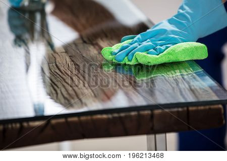Close-up Of A Janitor's Hand Wearing Gloves Cleaning Desk With Green Cloth