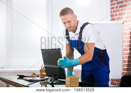 Young Male Janitor Cleaning Computer With Rag In Office