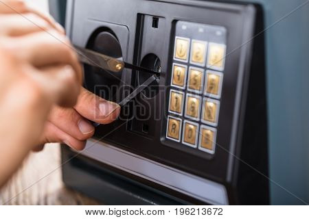 Close-up Of A Robber's Hand Trying To Break Home Safe