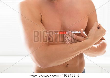 Shirtless Bodybuilder Man Using Steroids By Injecting Syringe In His Arm Against Black Background