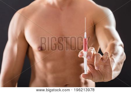 Close-up Of A Shirtless Bodybuilder Man Holding Syringe In His Hand Against Black Background
