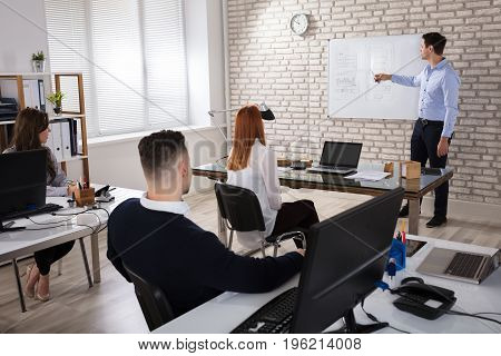Male Manger Giving Presentation To His Colleagues In Modern Office
