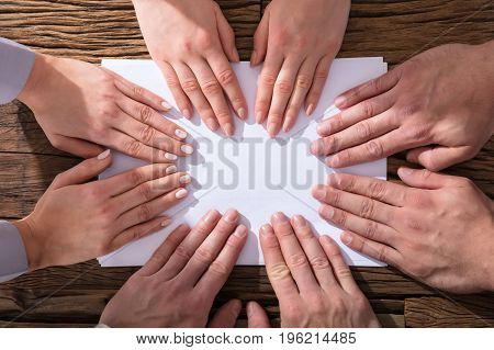 Close-up Of Hands Touching White Paper Over The Wooden Desk Showing Team Concept