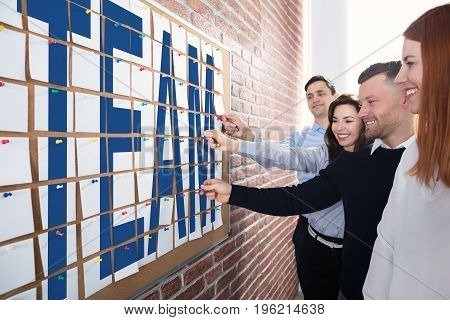 Business People Making Team Text On Adhesive Notes Over The Corkboard In Office