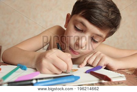 preteen handsome boy with crayons drawing close up photo