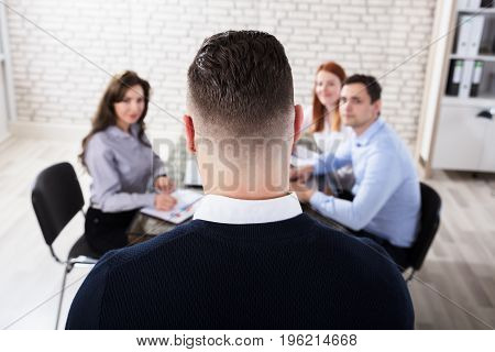 Rear View Of A Businessman Giving Presentation To His Employee In Office