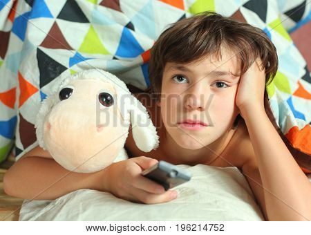 teenager boy watching tv with remote control and toy under duvet close up photo