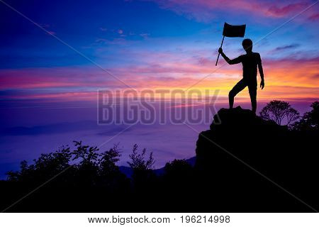 Silhouette of man holding flag standing on the mountain with success