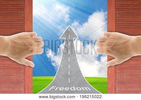 Two hands opening old wooden door to the new world. New life concept Freedom lifestyle.