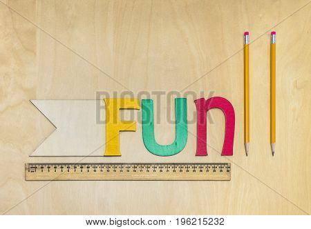 School Desk Surface With Wooden Letters Spelling Fun, Ruler, Pencils, And Flag