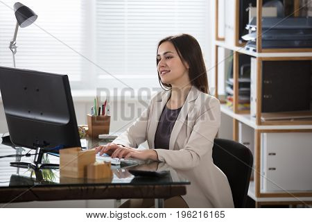 Young Smiling Businesswoman Typing On Keyboard In Office