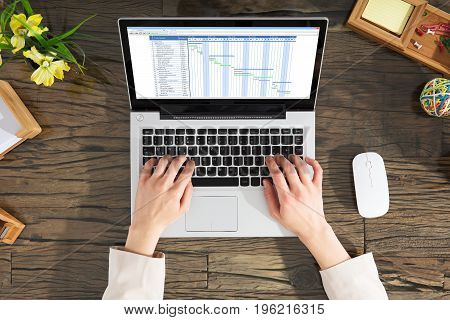 Close-up Of A Businessperson Analyzing The Gantt Chart On Laptop Over The Wooden Desk