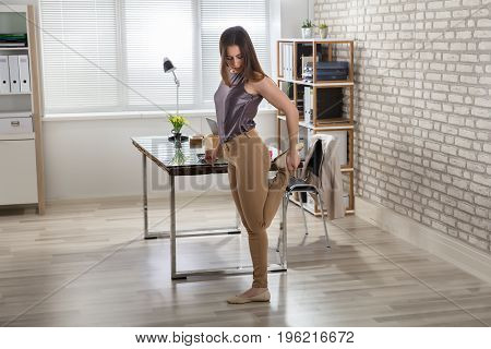 Young Businesswoman Stretching Her Leg At Workplace In Office