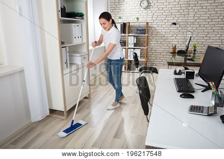 Happy Young Woman Cleaning The Floor With Mop In Modern Office