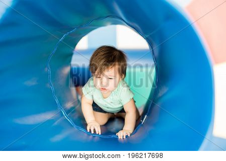 Beautiful baby girl working on early stimulation in a development center and exploring a tunnel in the playground
