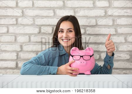 Portrait Of A Smiling Woman Behind The Heating Radiator Holding Piggy Bank