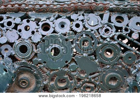 A Composition Of A Set Of Gears And Car Parts That Are Welded To Each Other And Painted Green. Grung