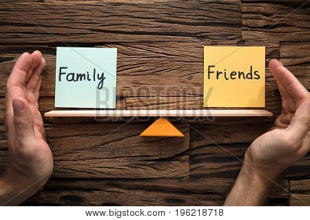 Closeup of hands covering balance between family and friends on seesaw against wood