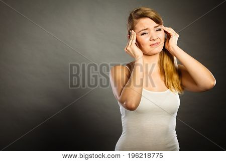 Health problem stress and depression. Woman suffering from headache migraine pain. Stressed female holds her head with hands