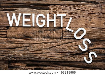 Closeup of white weight loss text on wood