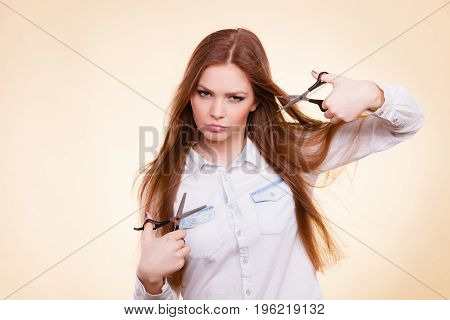 Irresponsibility danger haircut coiffure care beauty concept. Passionate female hairdresser. Cheerful lady dual wielding scissors showing her work tools normal and thinning shears