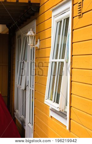 White Window And Antique Lantern On Yellow Cottage