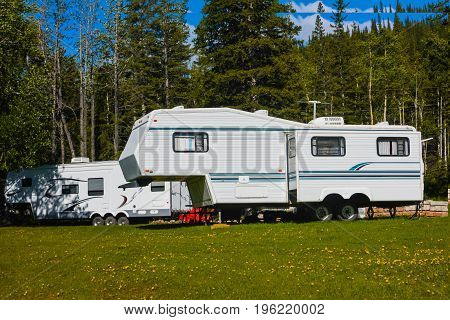 Trailer Caravan on a Green Field With Tall Trees at the Background