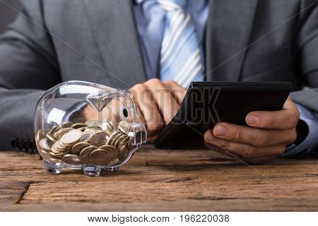 Closeup midsection of businessman using calculator by glass piggybank at table