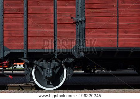 The Side Of The Old Brown Wooden Freight Car With The Wheel Of The Times Of The Soviet Union