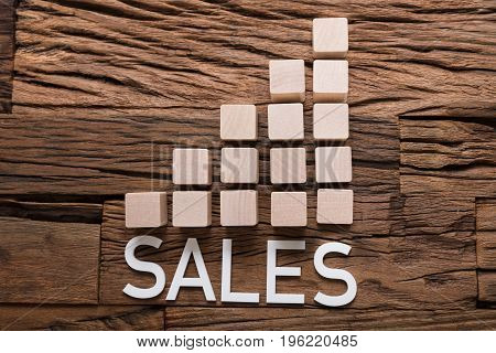 Closeup of sales text by increasing bar graph blocks on wooden table
