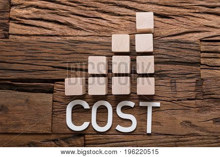 Closeup of cost text by increasing bar graph blocks on wooden table