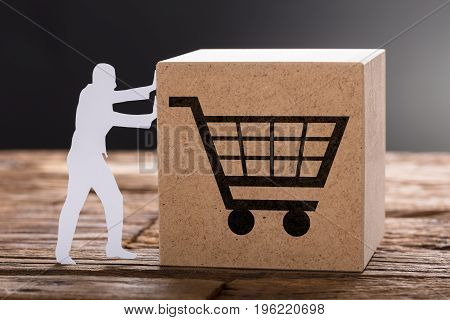 Closeup of paper man pushing wooden block with shopping cart on table against gray background
