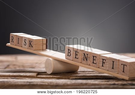 Closeup of risk and benefit wooden blocks on seesaw against gray background