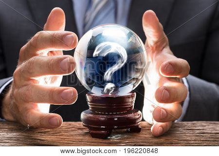 Midsection of businessman covering crystal ball with smoke forming question mark at wooden table
